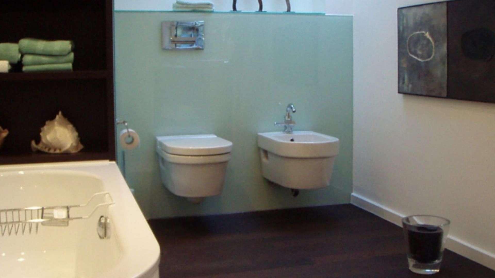 Glasrückwand hinter einer Toilette