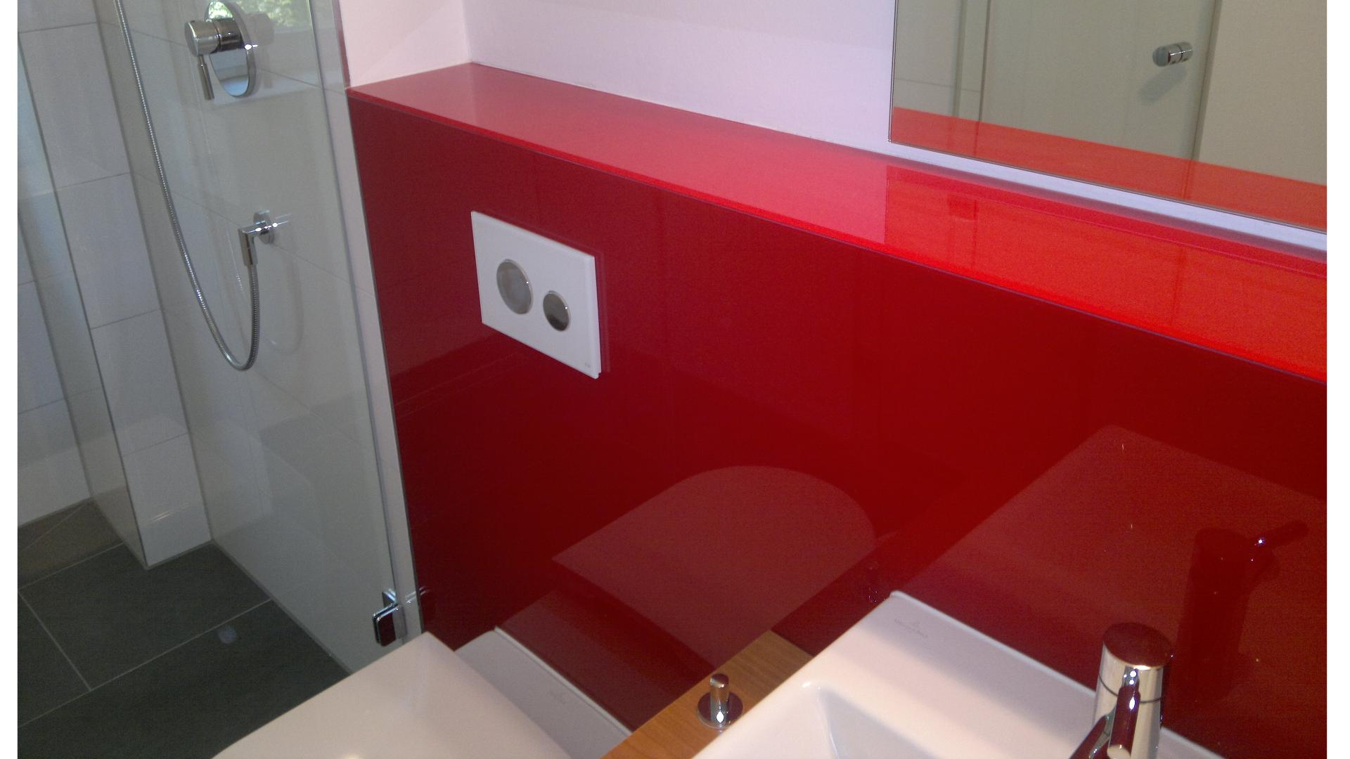 rote Glasrückwand hinter dem Waschtisch und Toilette eines Badezimmers