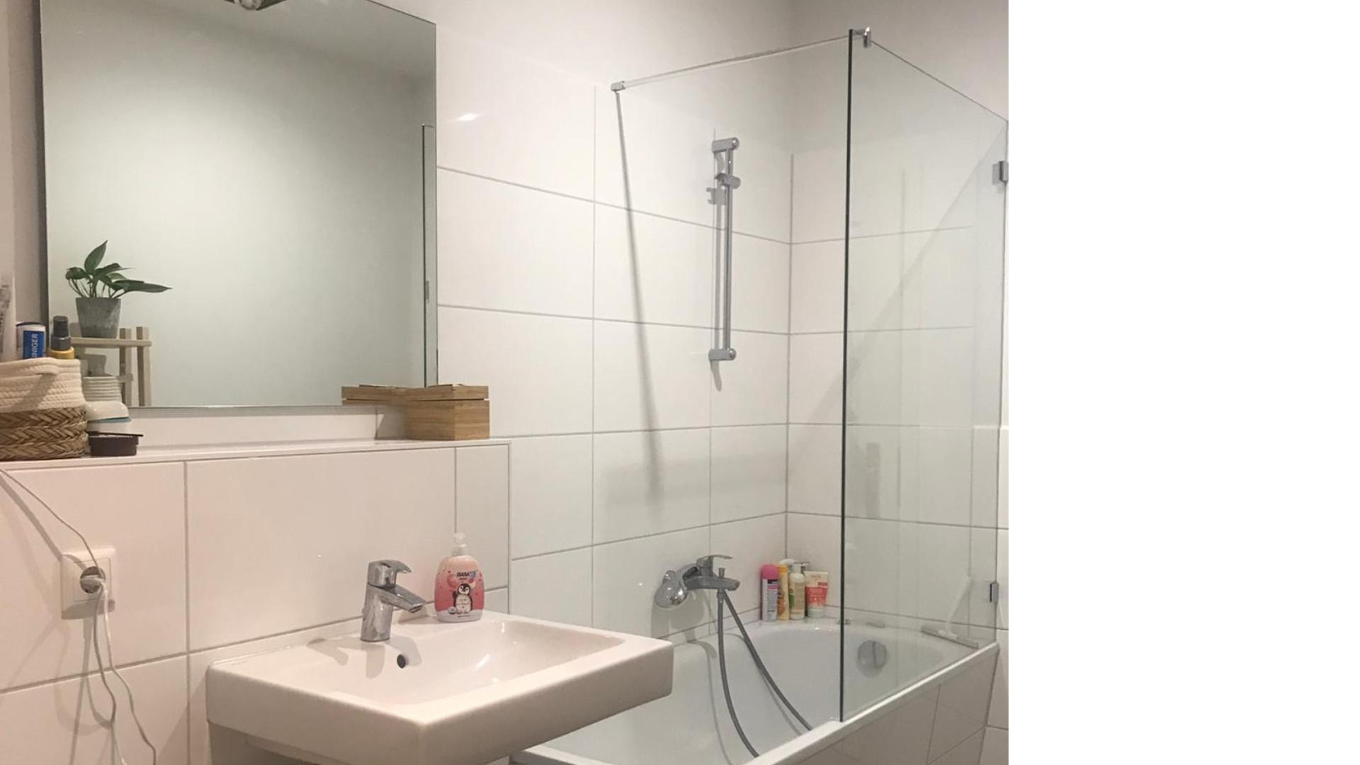 Duschwanne mit Glastrennwand neben einem Waschbecken