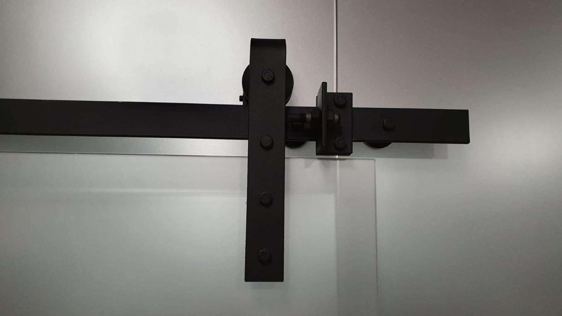 schwarzer Beschlag einer Schiebetür aus Glas