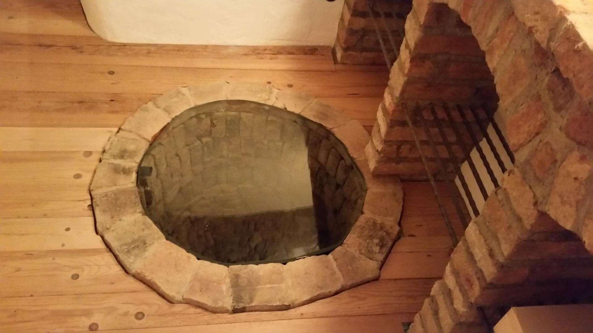 Brunnen im Keller, der mit einer Glasscheibe verdeckt ist
