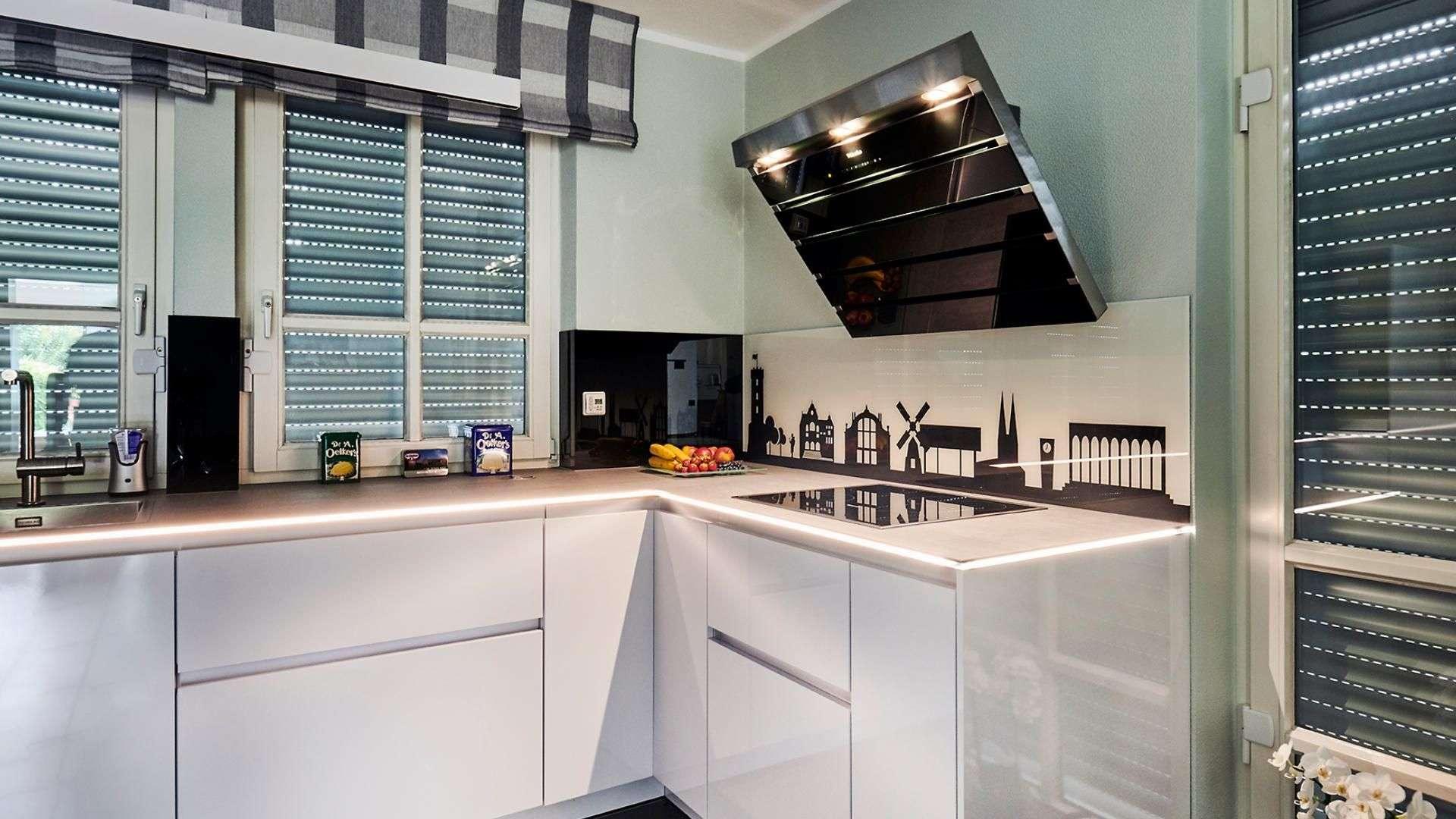 Küche mit beleuchteter Arbeitsplatte und Glasrückwand als Spritzschutz