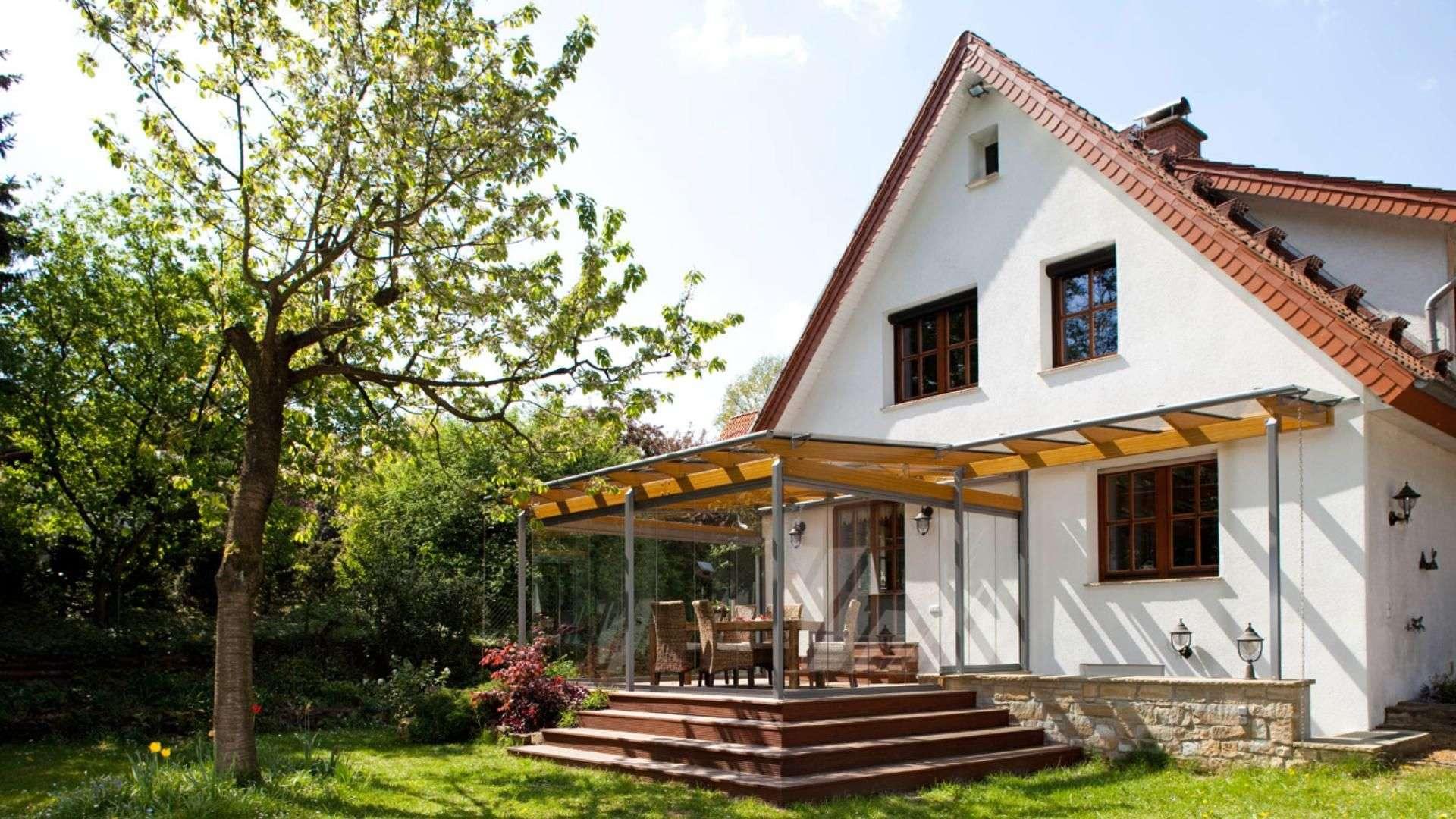 Terrassendach an einem Einfamilienhaus mit Garten
