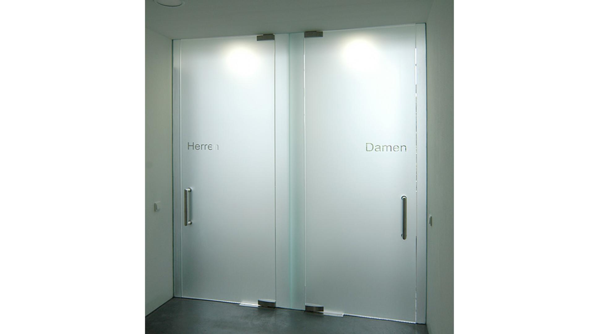 zwei Drehtüren aus Glas vor Toiletten