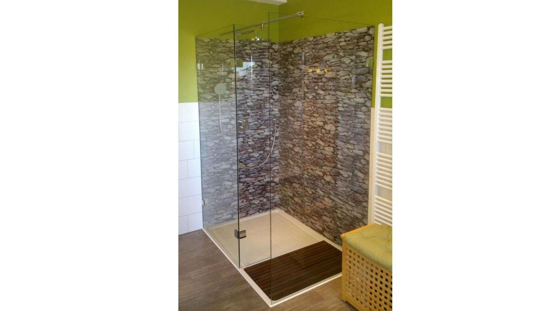 Dusche mit Glaswänden vor einer Steinwand