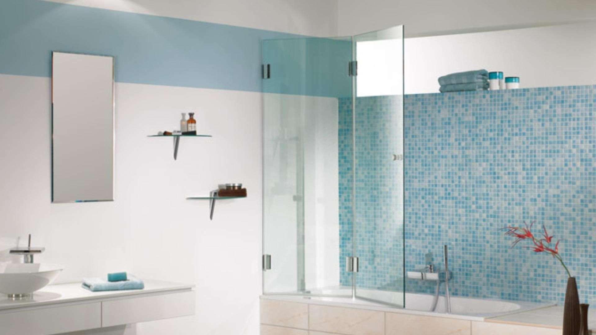 Duschwanne mit kurzer Glastrennwand in einem hellblauen Badezimmer