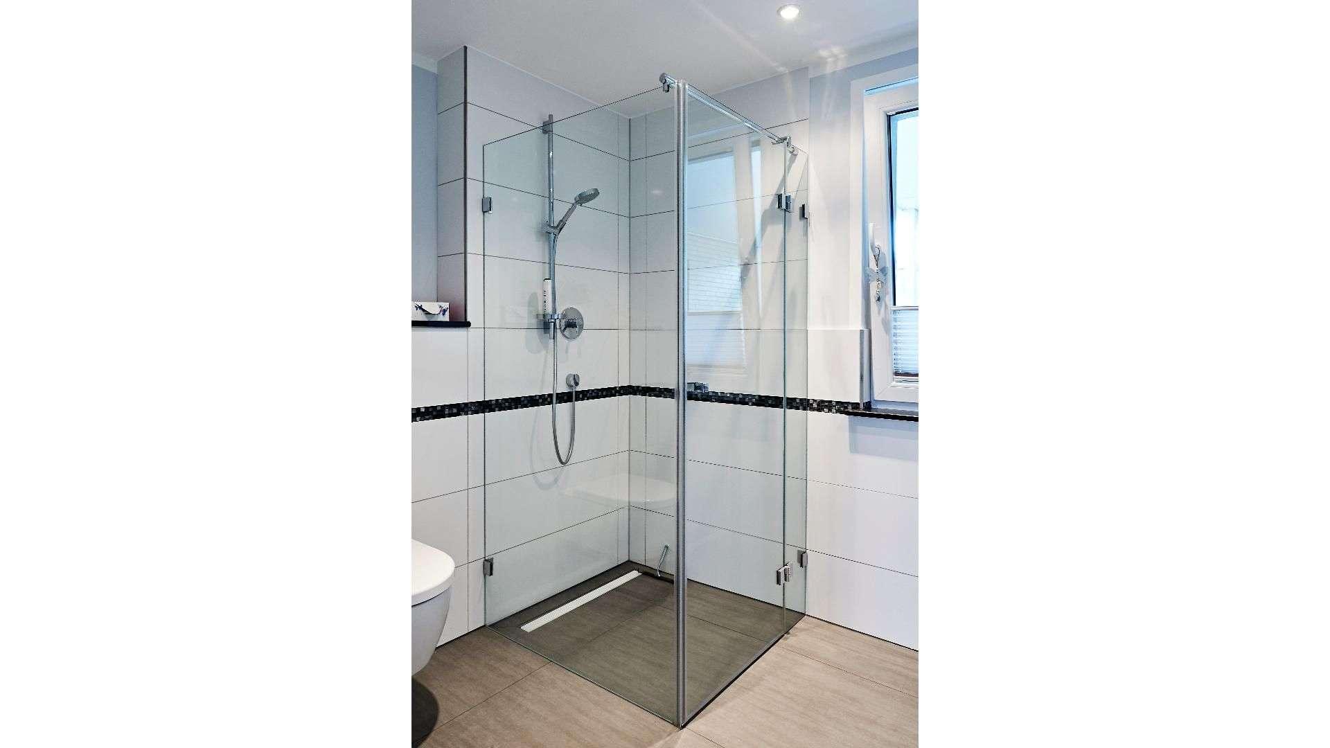 Dusche mit Glastür in einem Badezimmer