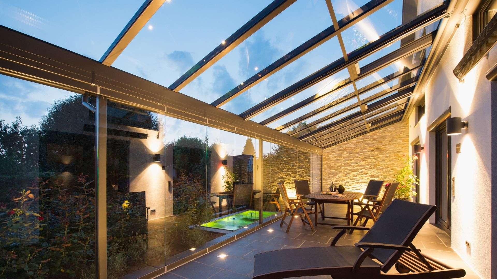 Innenansicht eines beleuchteten Glashauses mit Esstisch und Liegestuhl