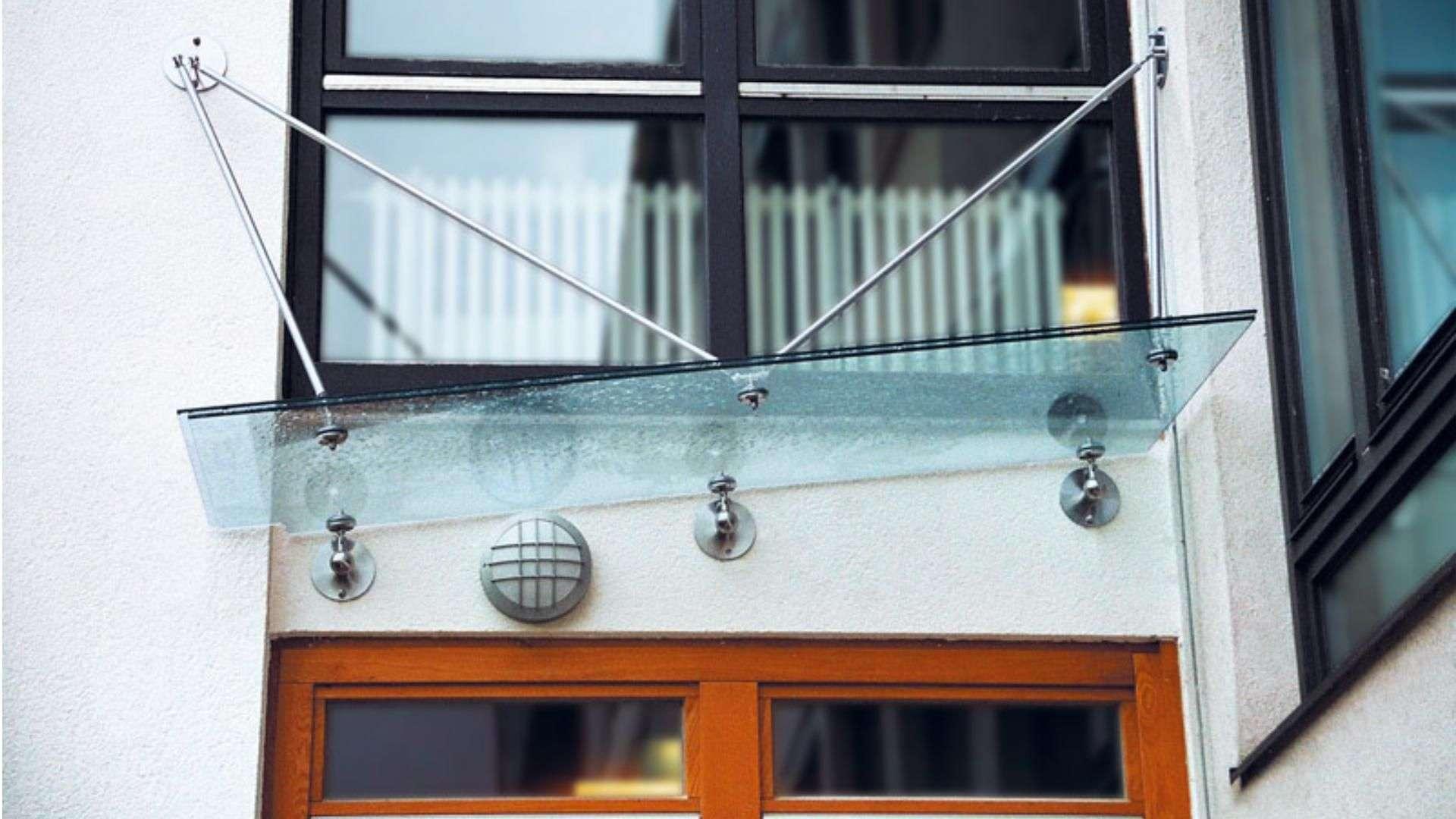 schräges Vordach aus Glas über einer Tür