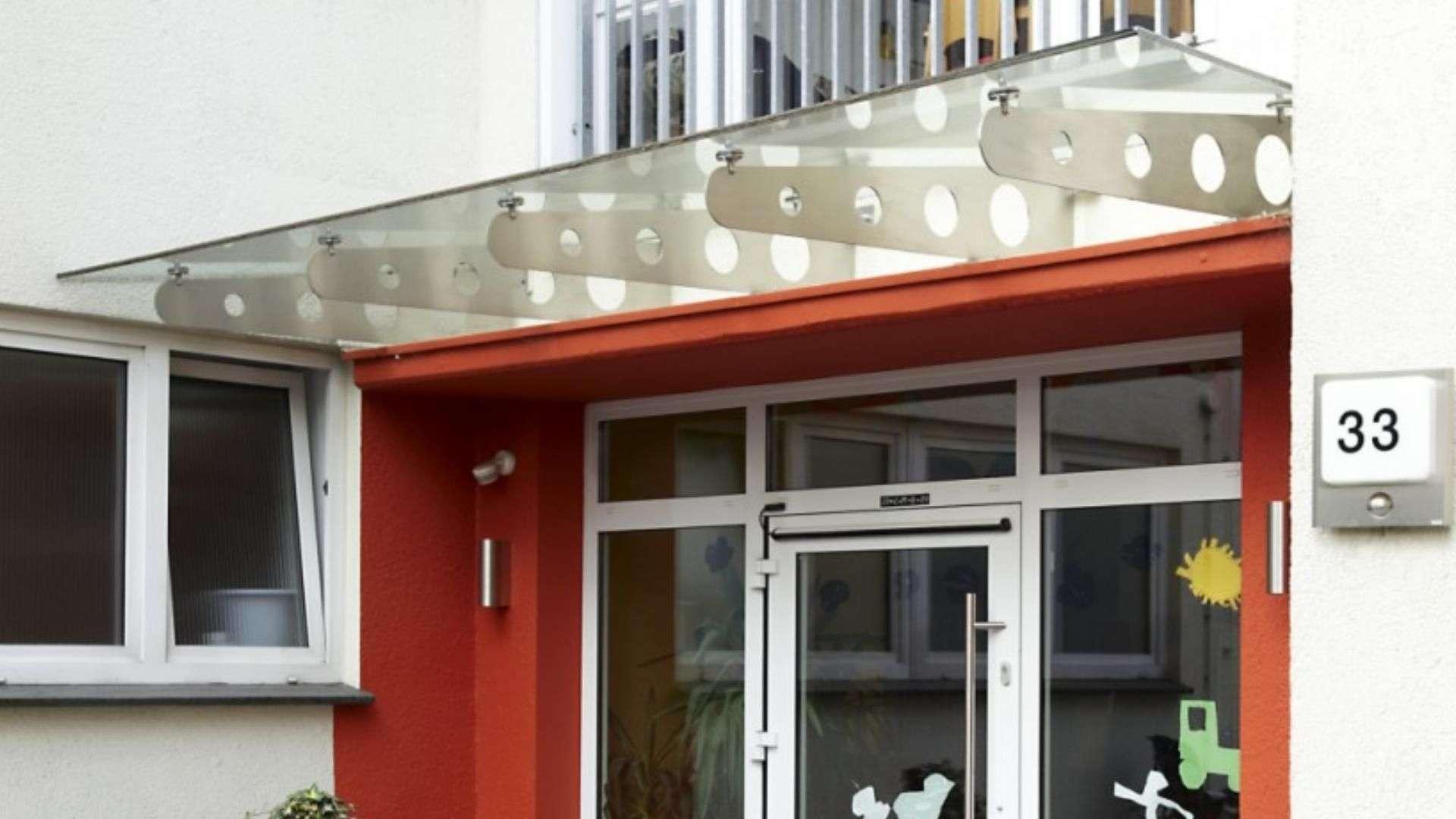 Vordach aus Glas über einer weißen Haustür