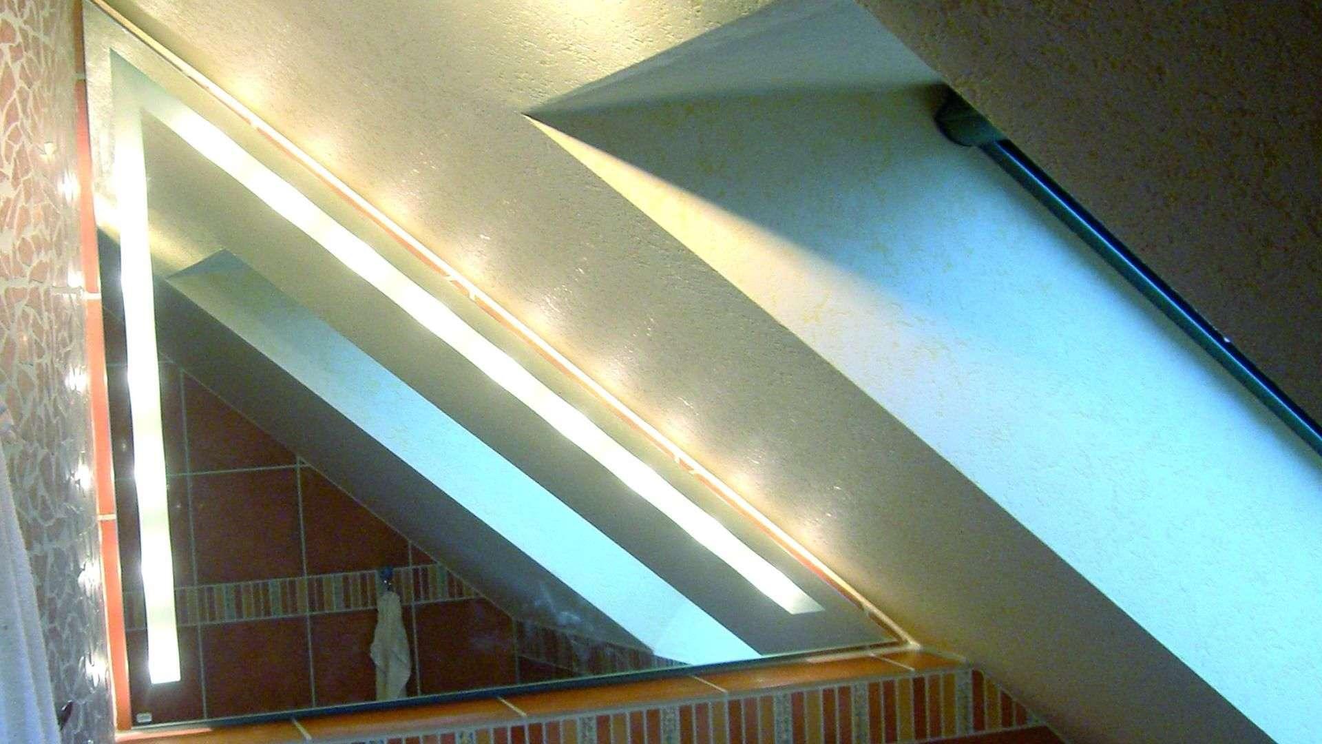 beleuchteter dreieckiger Spiegel unter einer Dachschräge