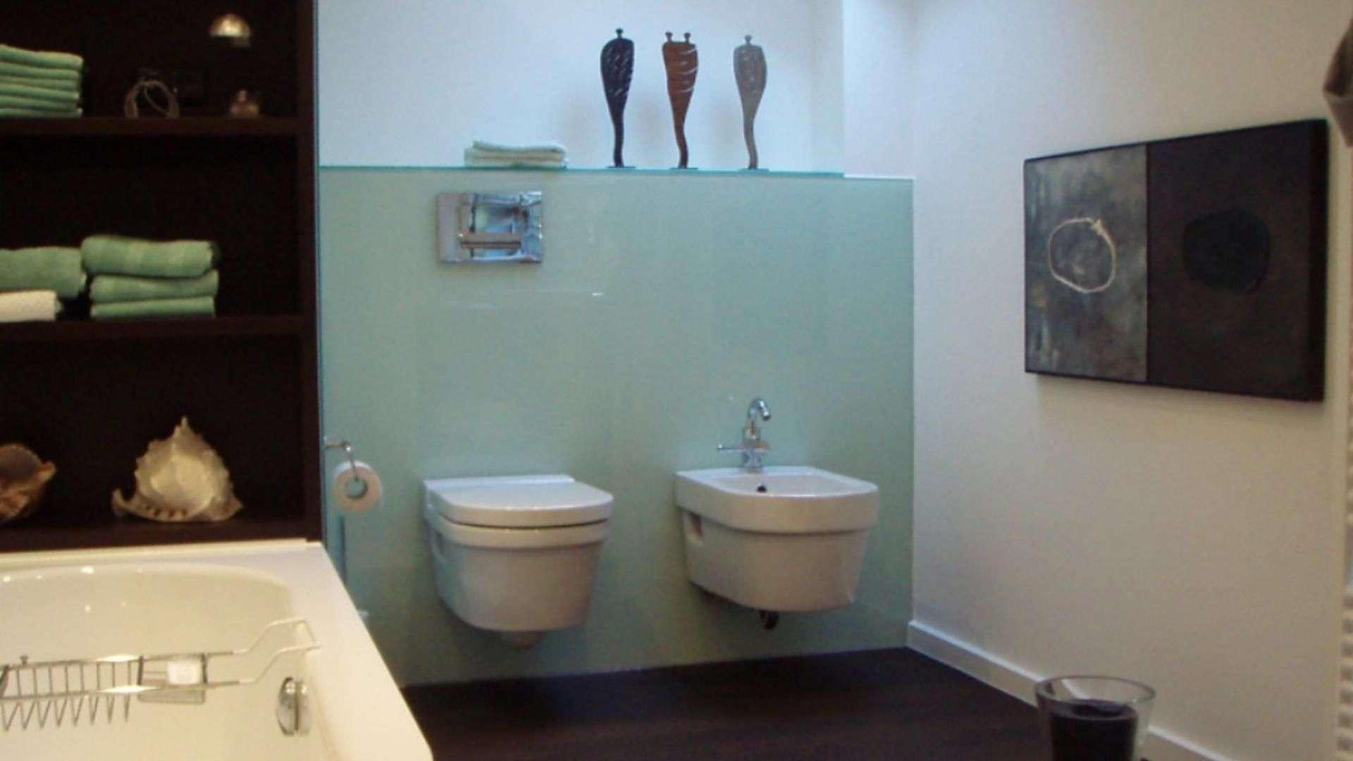Glasrückwand im Badezimmer hinter einer Toilette