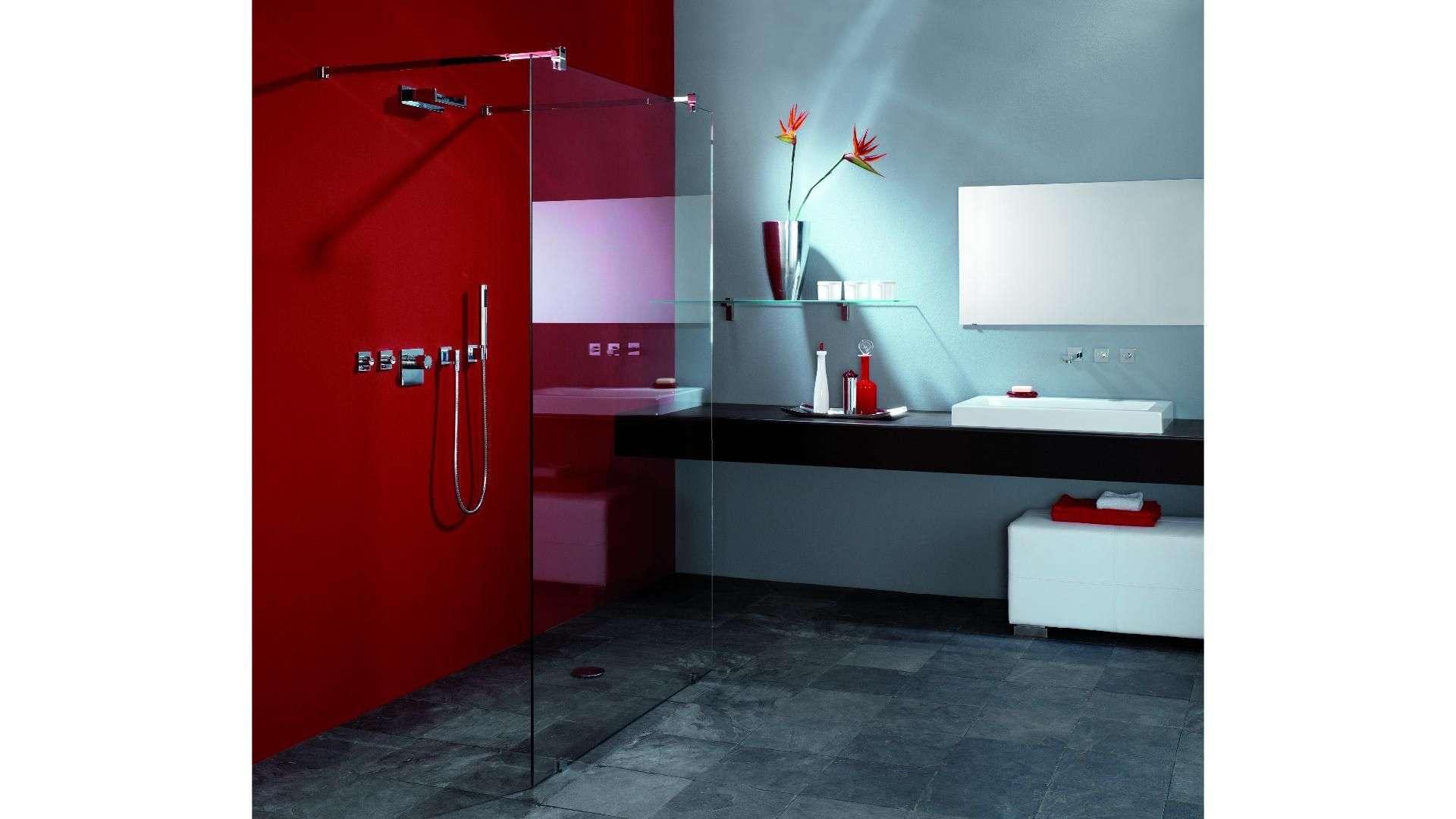 Dusche vor einer roten Wand mit Glastrennwand