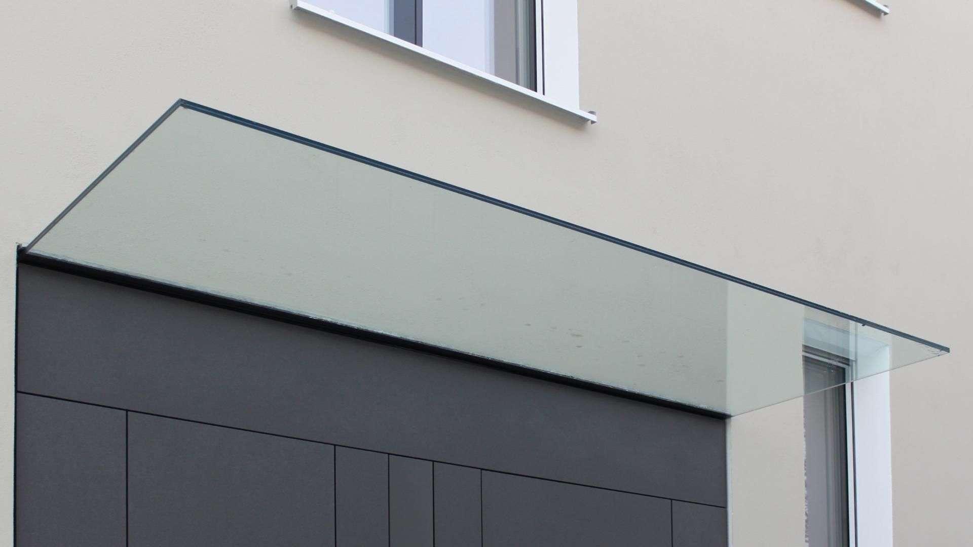 Vordach aus Glas über einer grauen Haustür