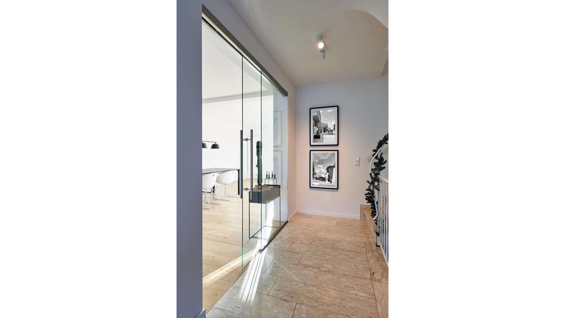 Seitlicher Blick auf eine doppelflügelige Glastür zwischen zwei Räumen