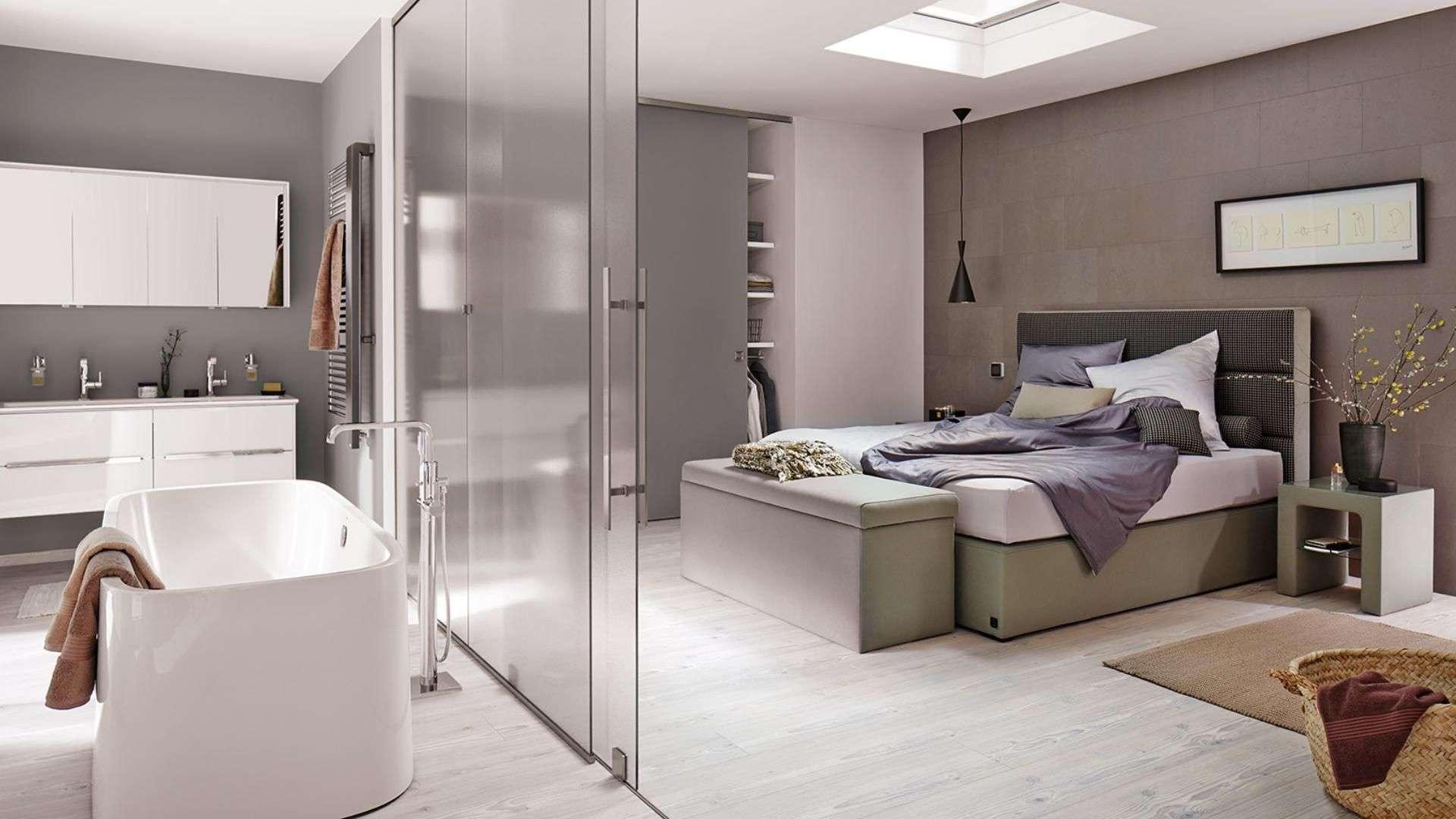 Schlafzimmer mit Glas-Trennwand zum Badezimmer