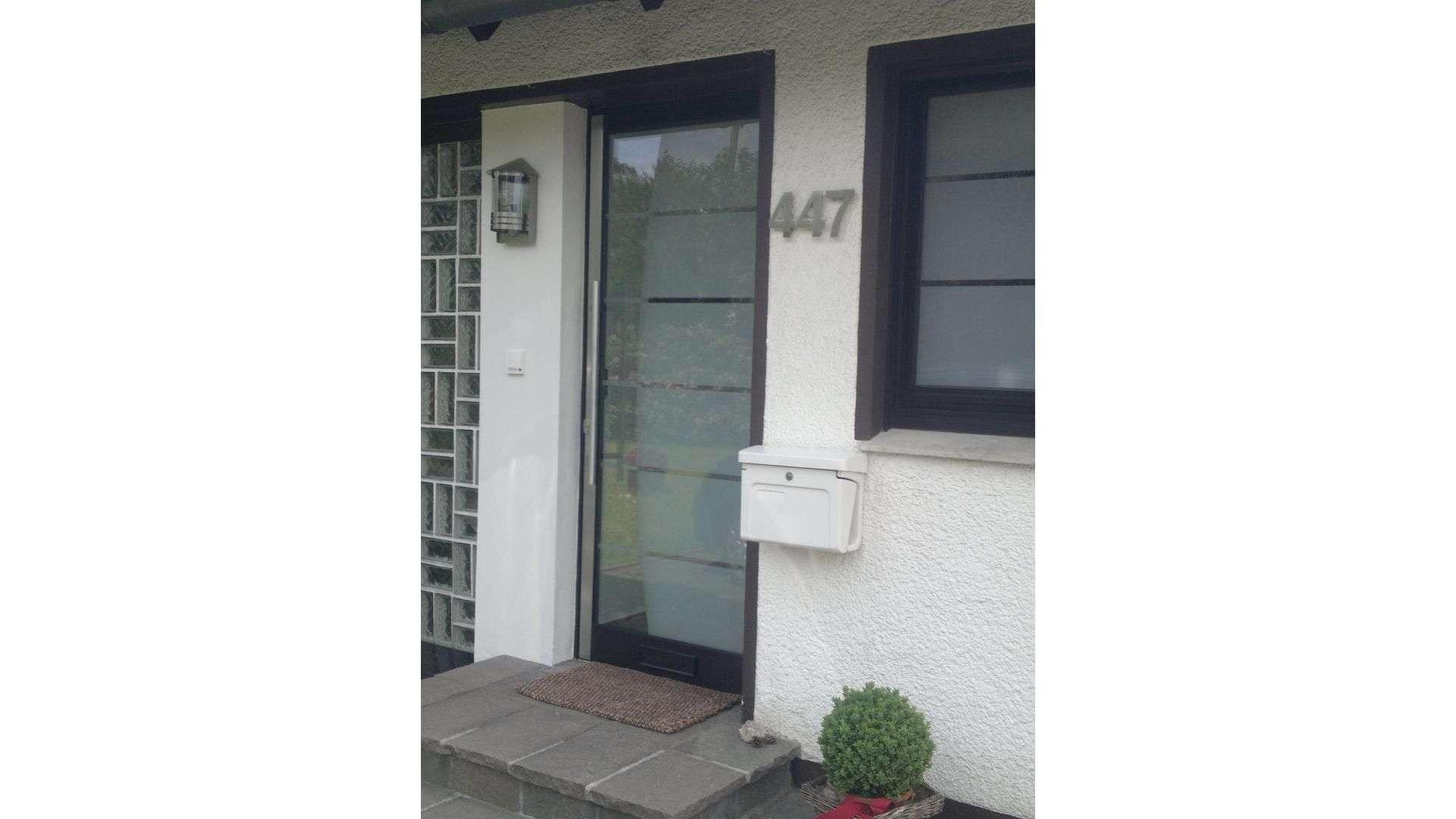 Haustür mit Glaseinsätzen in weißer Fassade