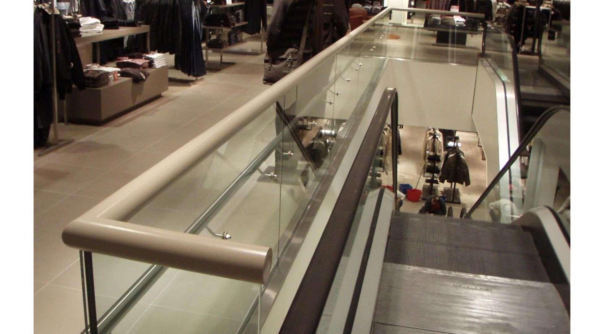 Glasgeländer um ein Treppenhaus mit Rolltreppen
