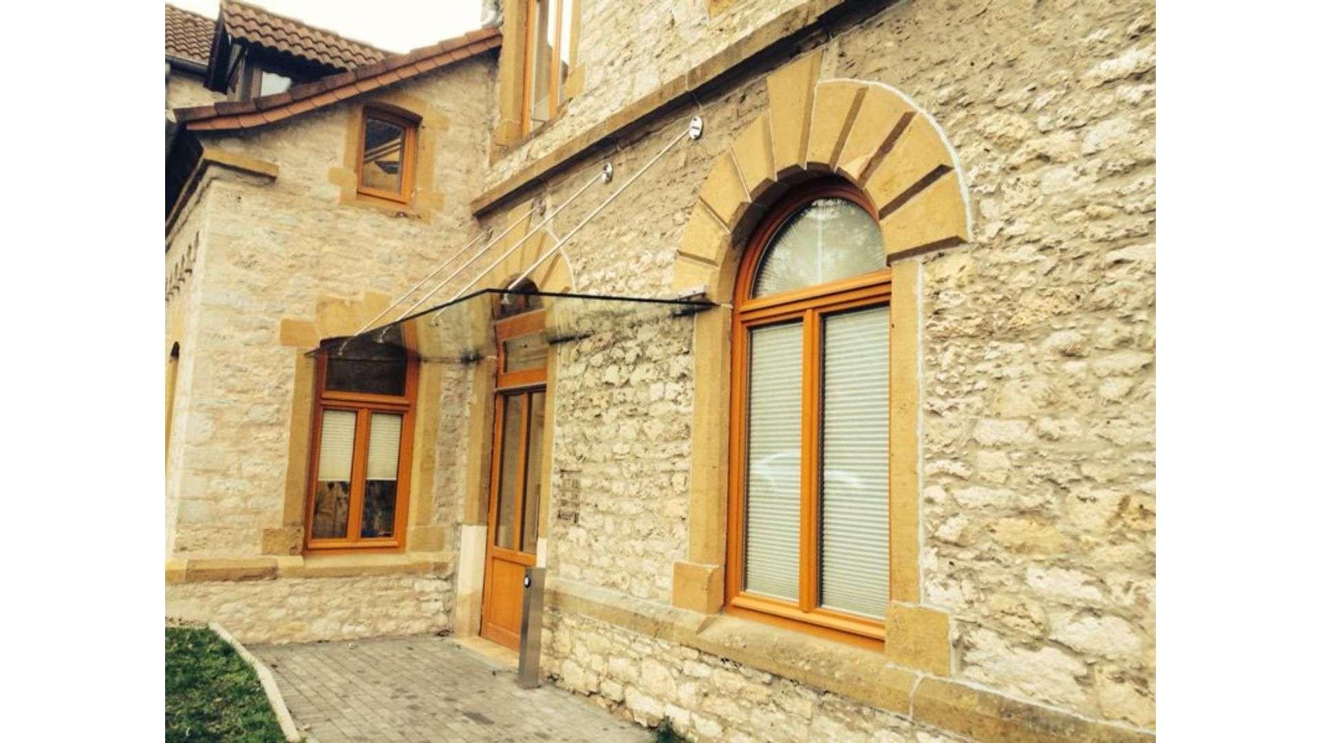 Glasvordach an einem Steinhaus