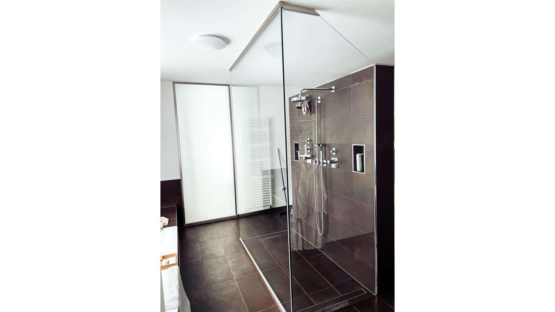 freistehende Dusche mit Glas-Trennwand in einem Badezimmer