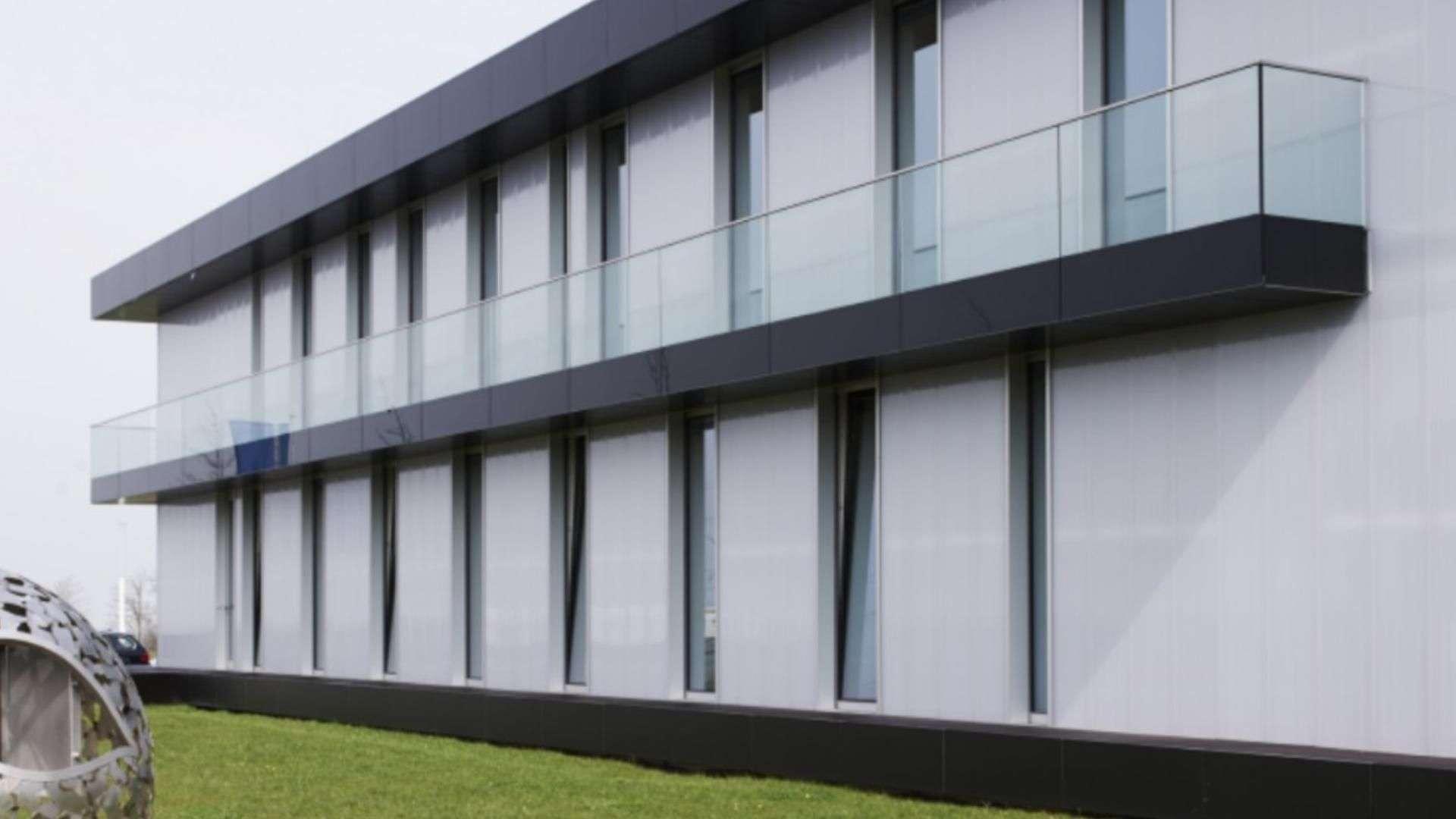 langer Balkon mit Glas-Geländer an einem Gebäudekomplex