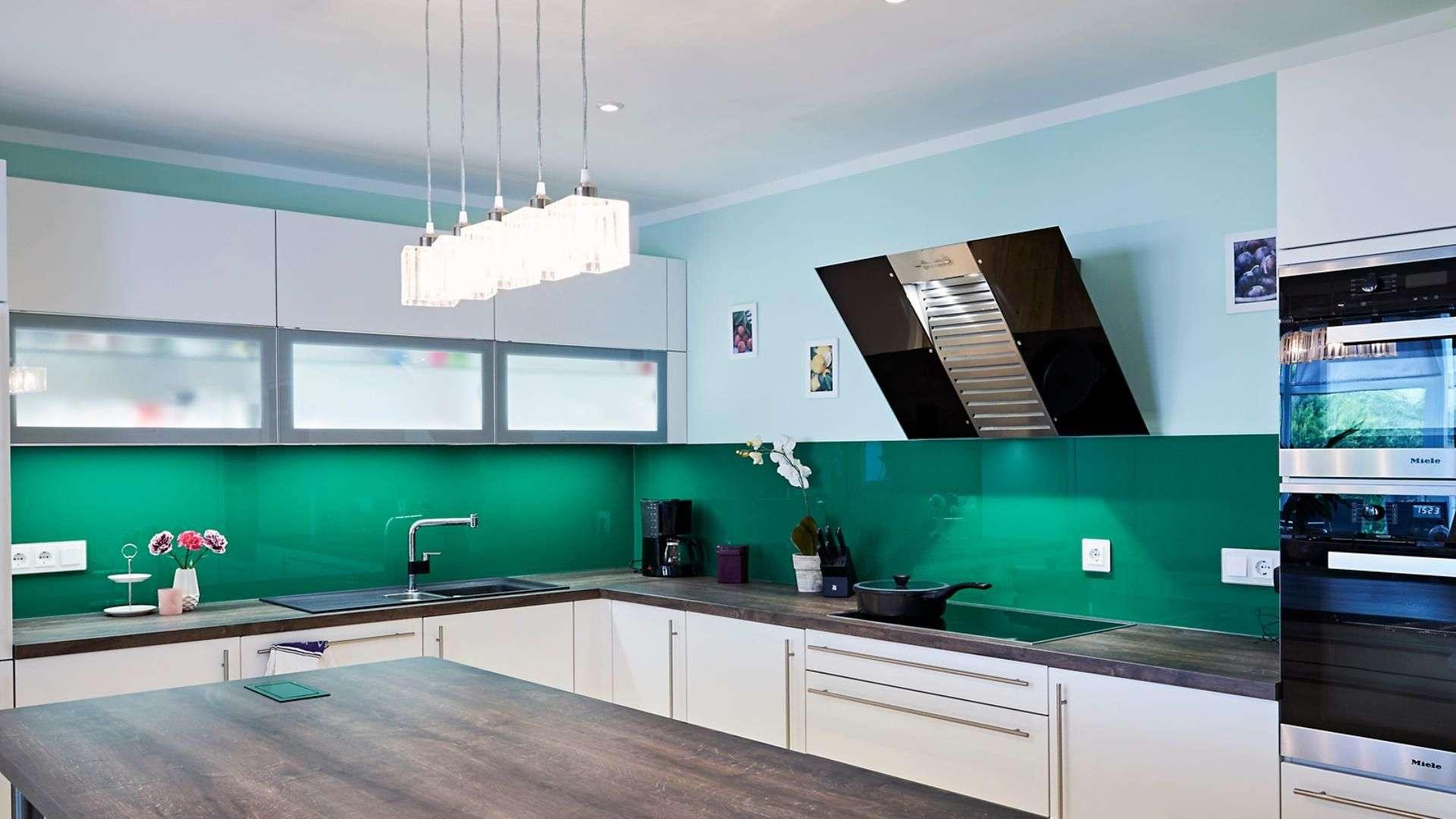 grüne Glasrückwand als Spritzschutz in einer Küche
