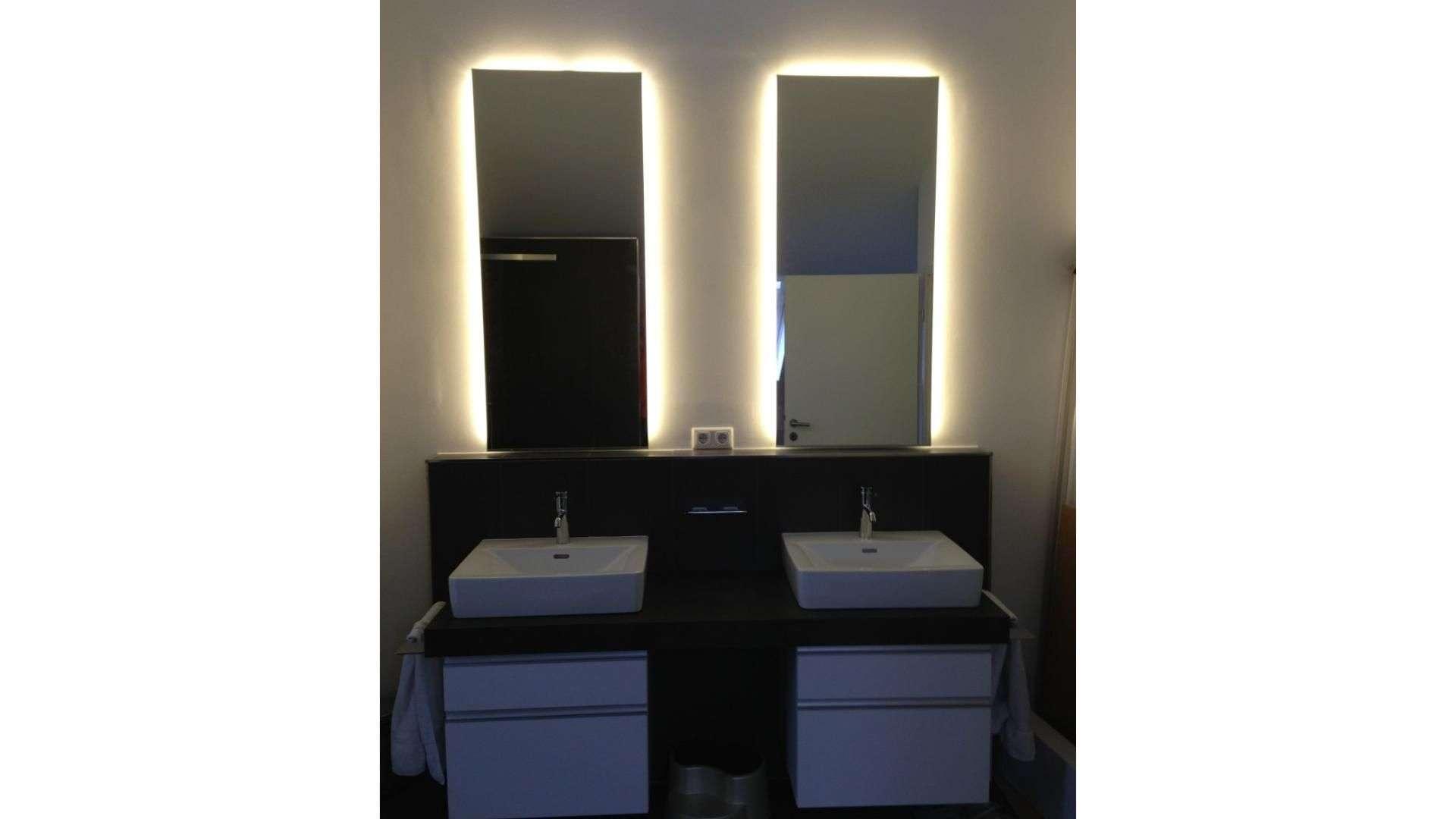 zwei beleuchtete Spiegel über zwei Waschbecken