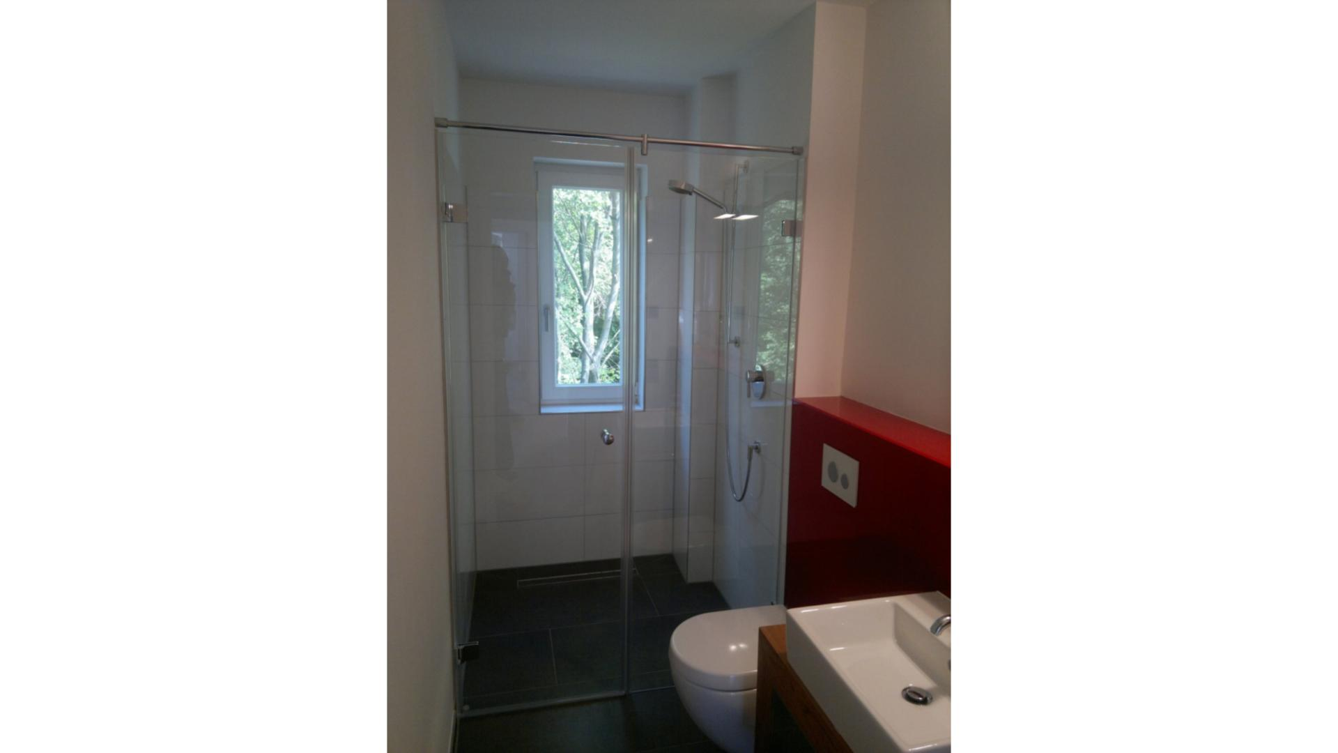 Dusche mit Glastür in einem schmalen Badezimmer