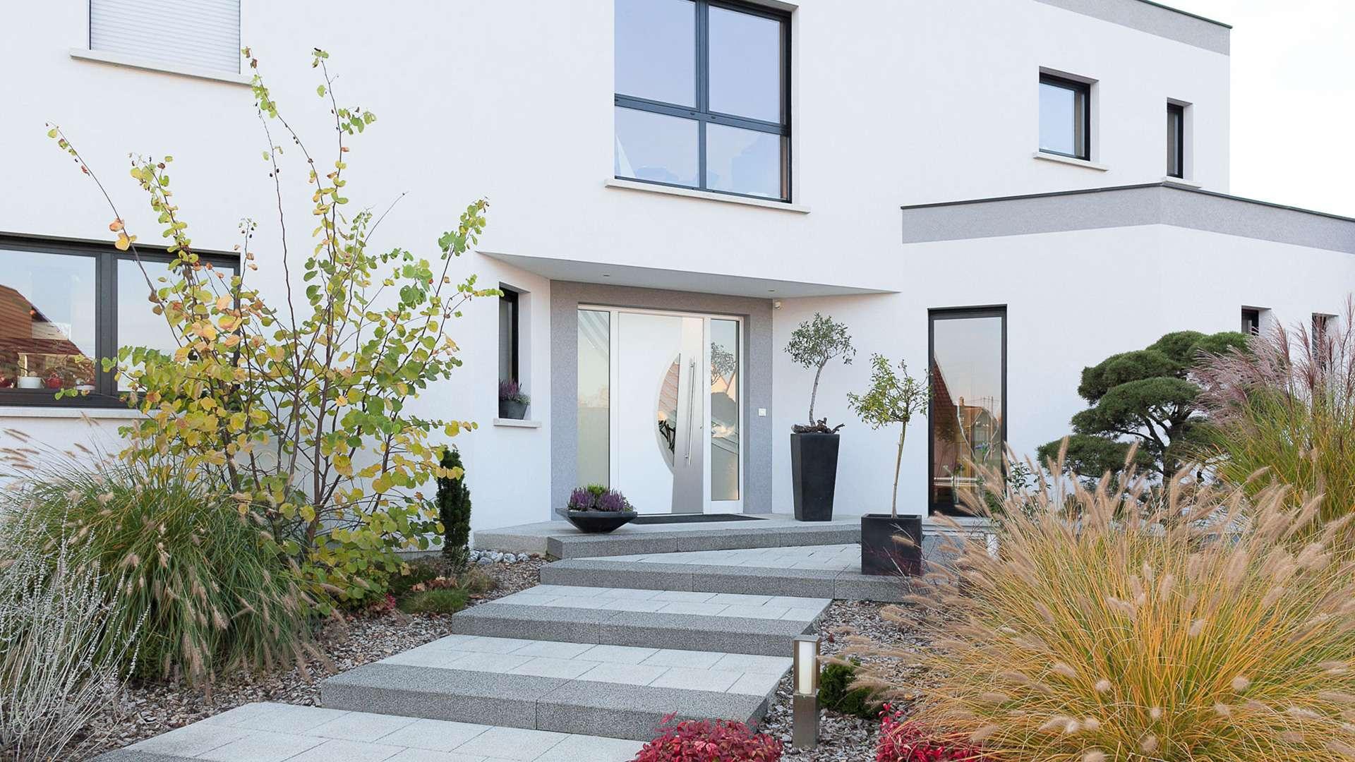 weiße Aluminium-Haustür mit Glaselementen auf beiden Seiten in einem weißen Haus