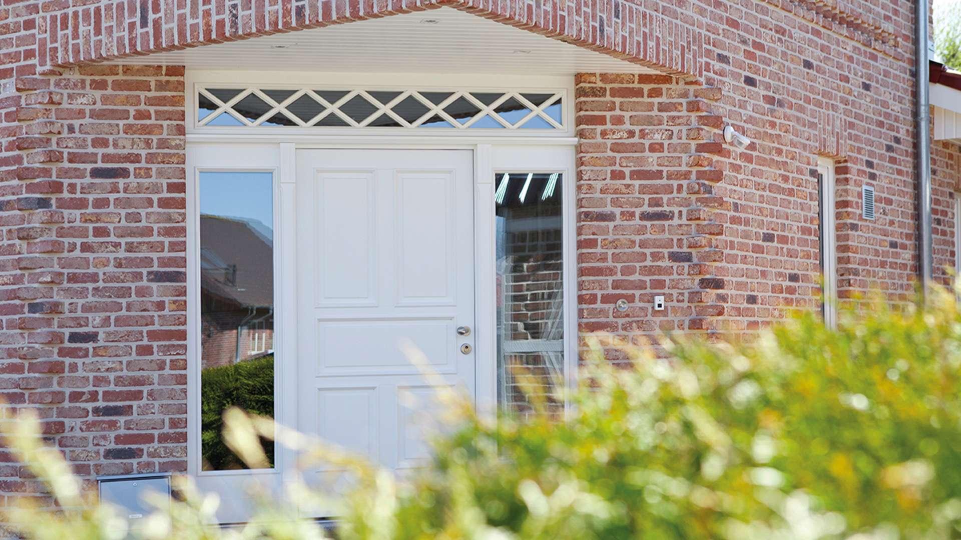weiße Holz-Haustür mit Glaselementen auf beiden Seite in rotem Klinker