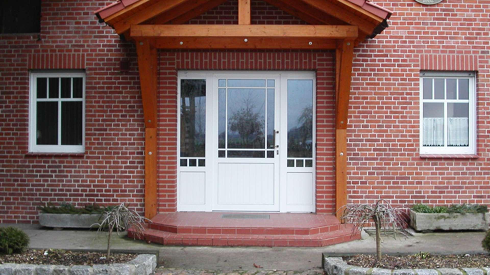 weiße Kunststoff-Haustür mit Vordach in rotem Klinker