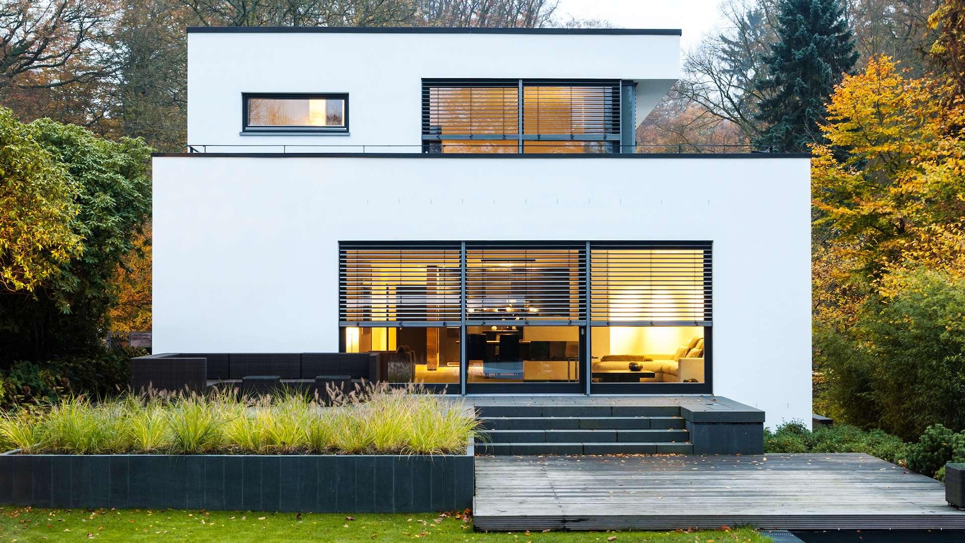 Flachdach-Haus mit Raffstoren vor den bodentiefen Fenstern