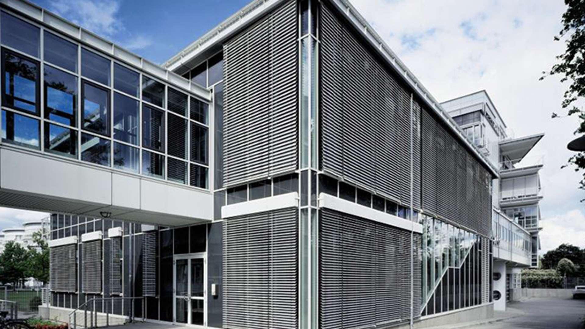 Geschäftsgebäude mit Raffstoren vor der Glasfassade