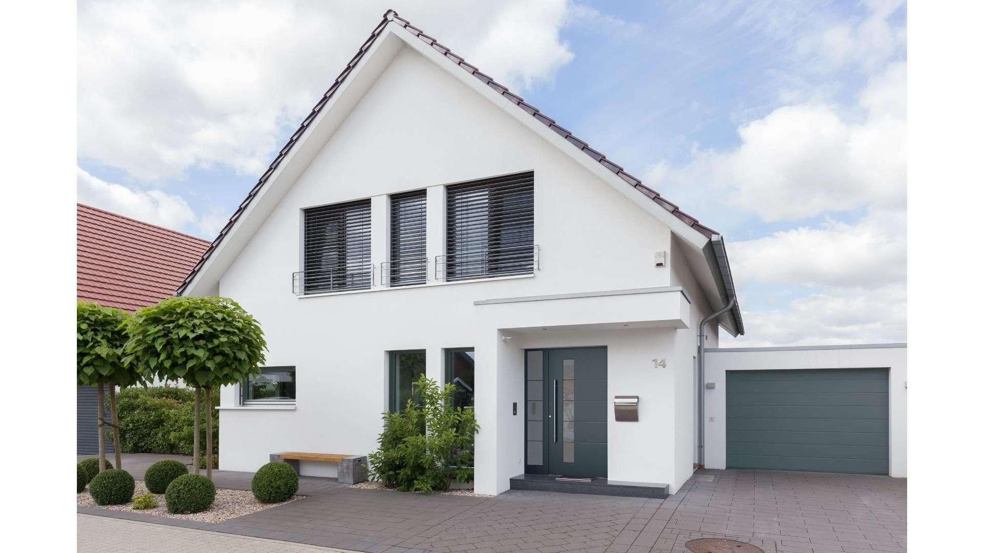 graue Haustür mit Glaselement auf der linken Seite in einem weißen Haus
