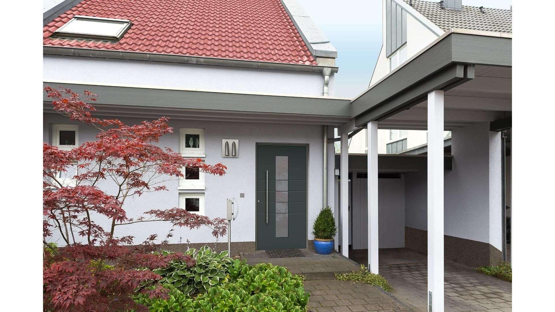 graue Haustür neben einem Carport