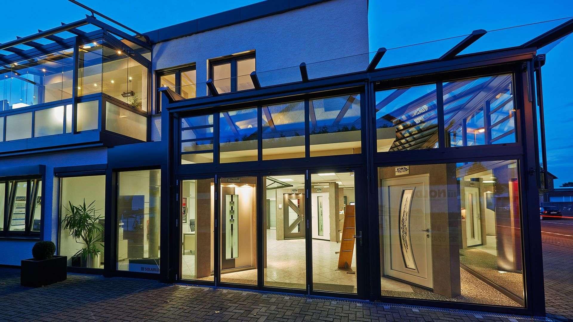 Blick von außen in die Nolden Ausstellung bei Nacht. Drinnen ist die Türenausstellung hell erleuchtet.