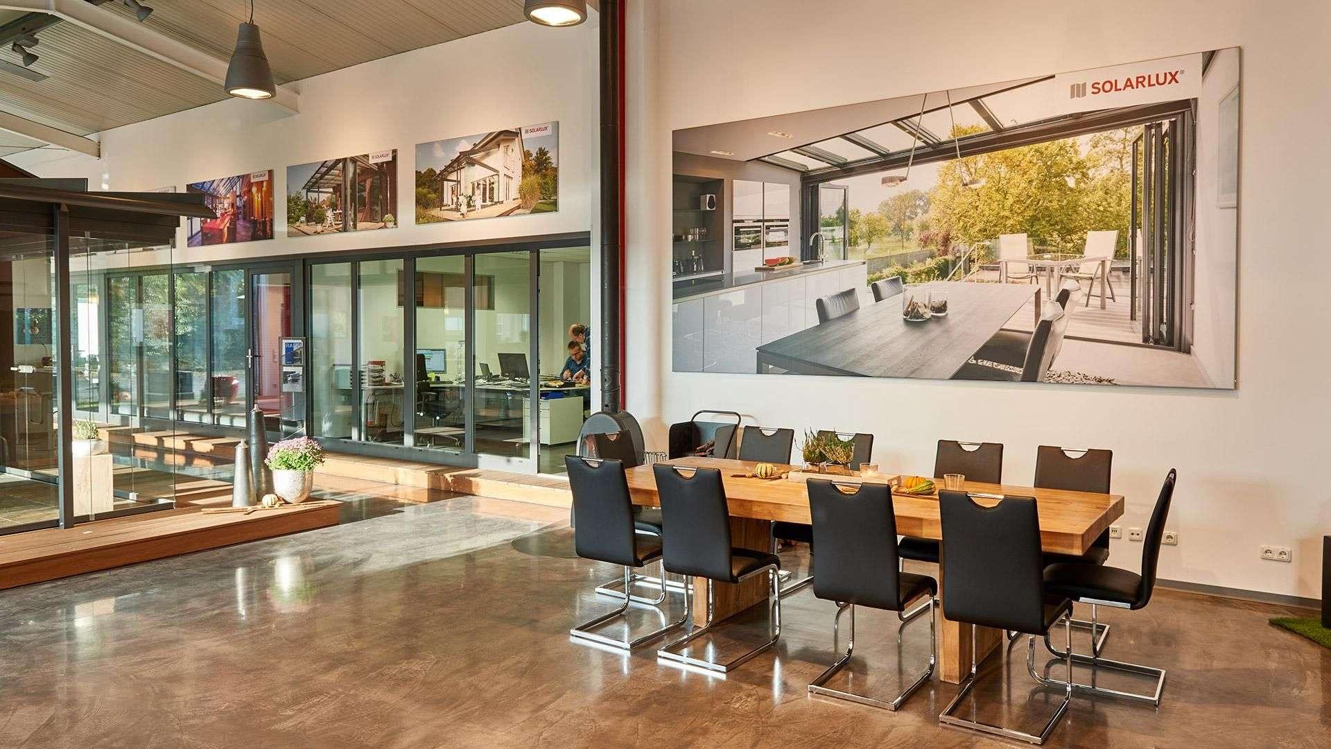 Konferenztisch in der Nolden Ausstellung mit Solarlux-Wintergarten-Bild an der Wand