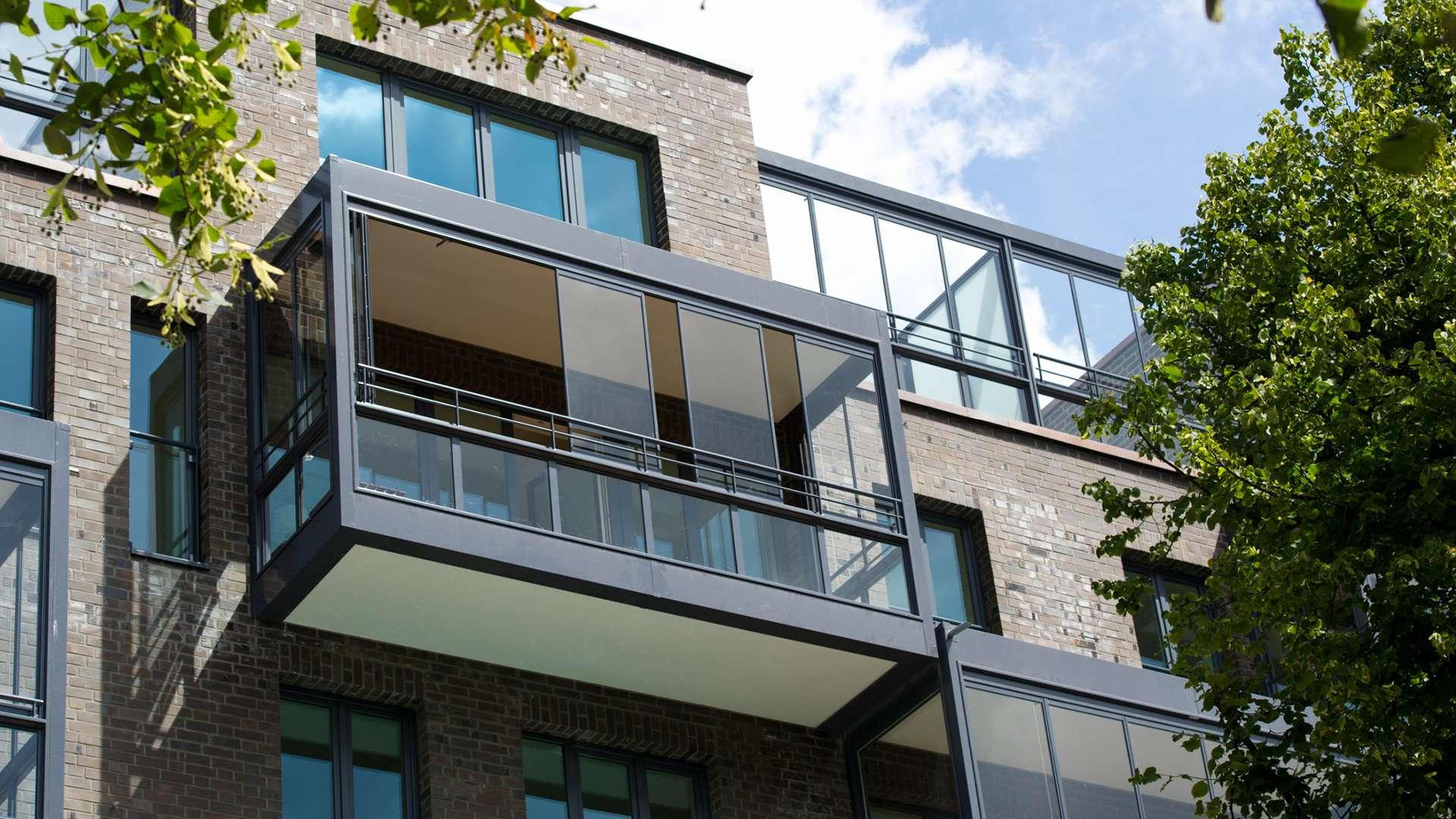 Balkonverglasung in einem oberen Stockwerk an einen Mehrfamilienhaus