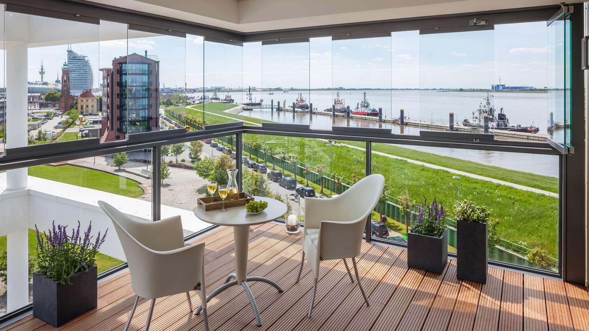 Blick auf einen verglasten Balkon, von dem aus man auf einen Fluss guckt