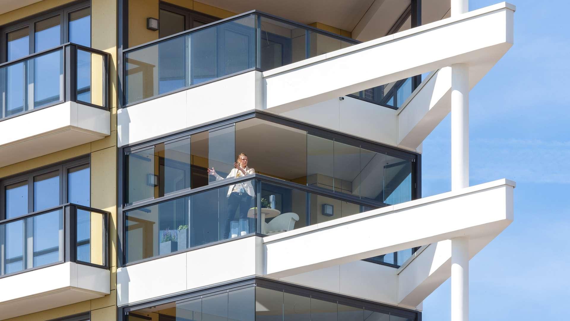 Mehrfamilienhaus mit einem verglasten Balkon, auf dem eine Frau steht