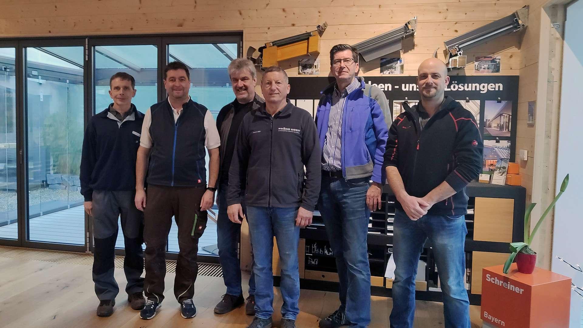Gruppenbild Berufsschullehrer mit Franz Ober in der Ausstellung der Schreinerei Ober in Neuötting