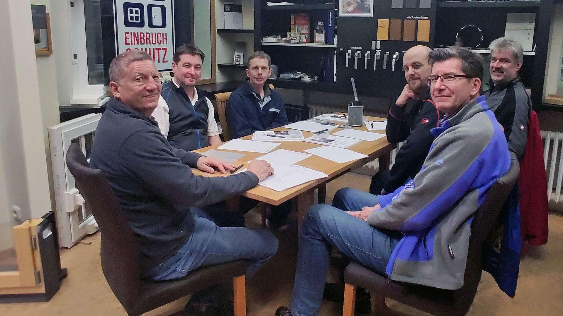 Gruppenbild Berufsschullehrer sitzen mit Franz Ober an einem Tisch in der Ausstellung der Schreinerei Ober in Neuötting