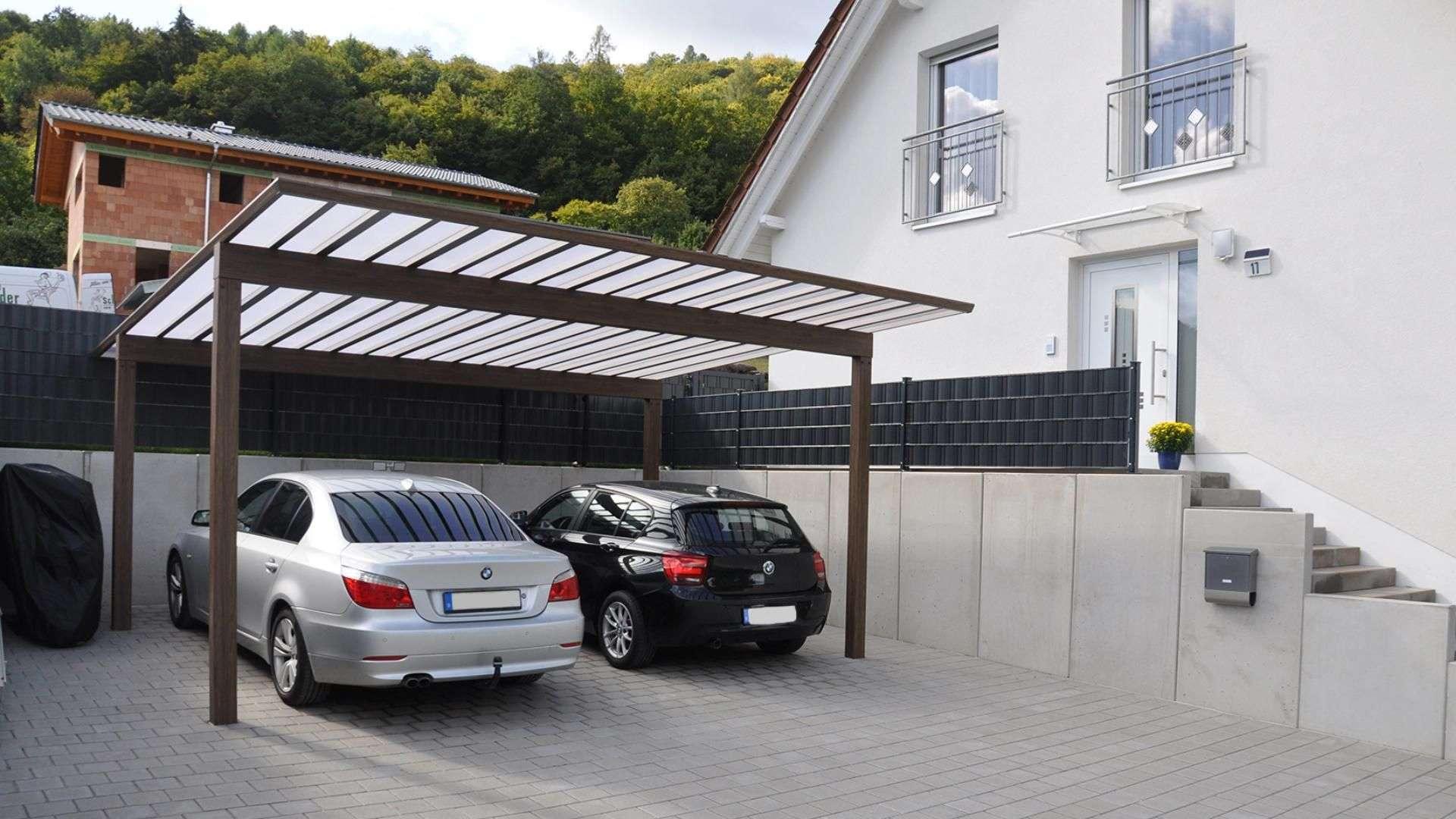 zwei Autos unter einem Carport Artport neben einem Wohnhaus