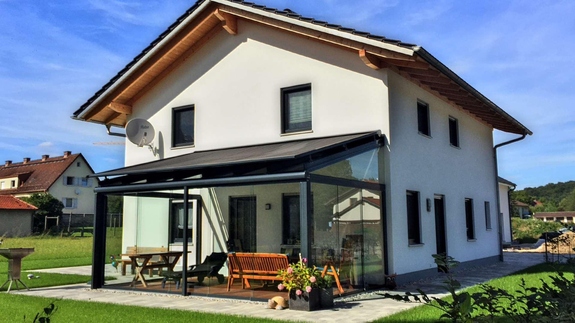 weißes Wohnhaus mit Glashaus mit Aufglasmarkise auf der Terrasse und großem Garten