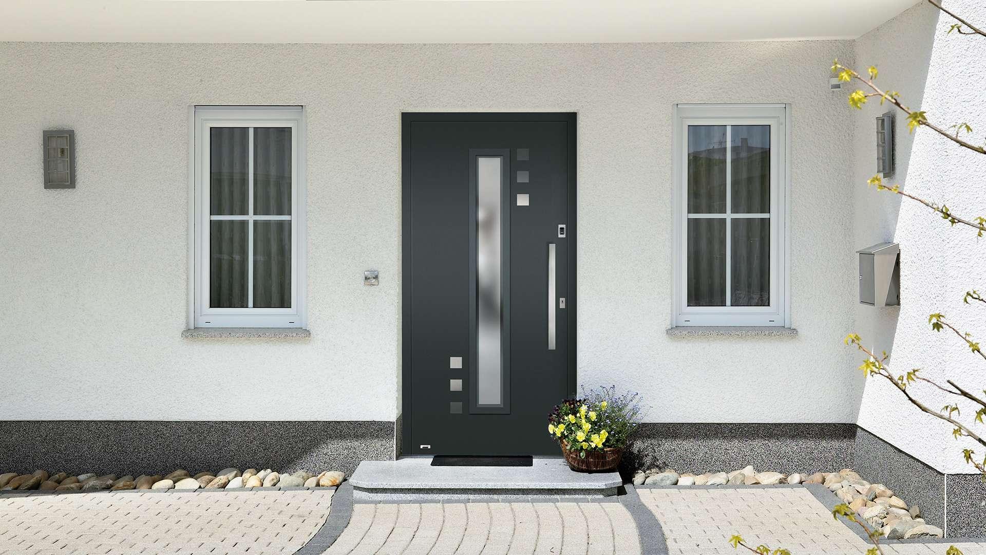 graue Haustür in weißer Fassade mit zwei Fenstern links und rechts und einen gepflasterten Hof