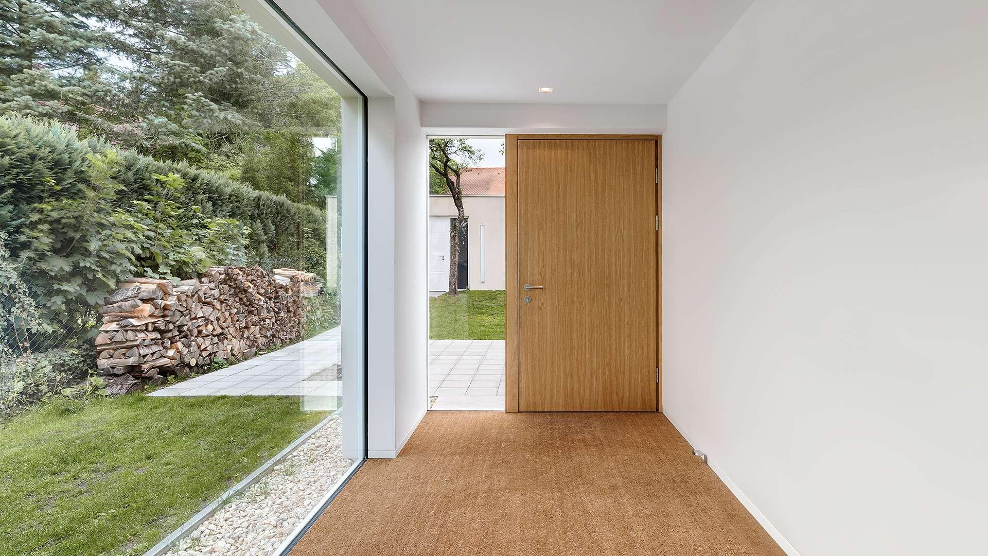 Eingangsbereich mit eine Holzhaustür und langer Glasfront an der linken Seite zum Garten hin