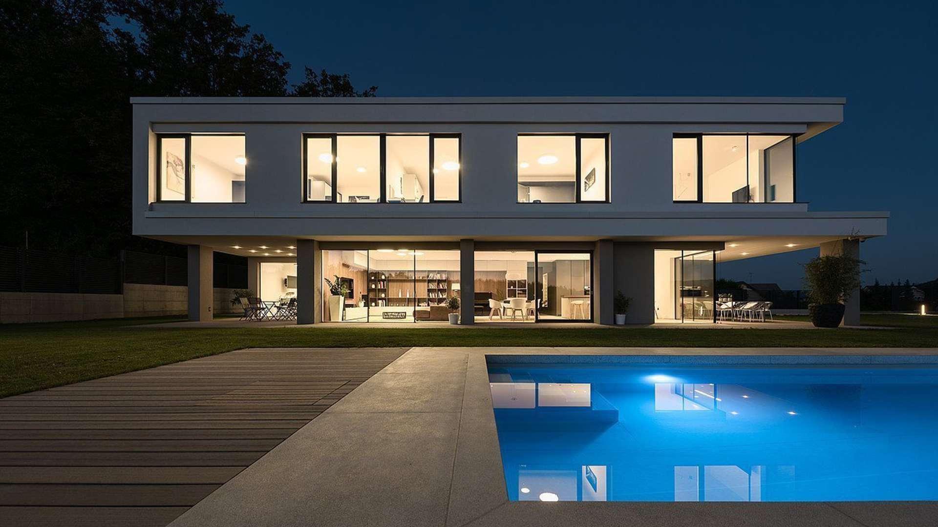 modernes großes Wohnhaus mit Flachdach und vielen Holzalufenstern bei Nacht. In Inneren des Hauses brennt Licht und im Vordergrund sieht man einen Pool.