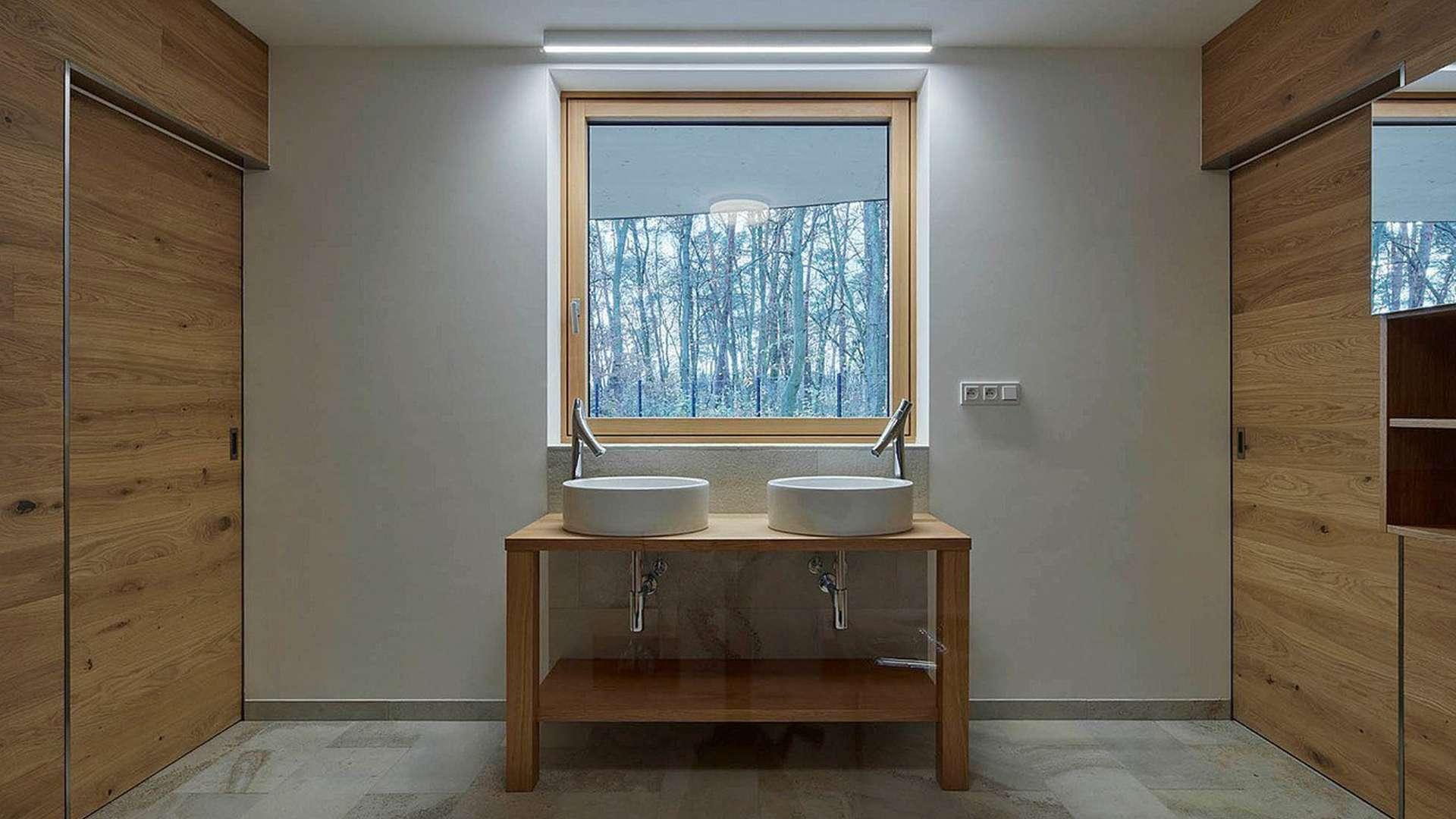 Badzimmer mit Blick auf ein Holzalufenstern mit zwei Waschbecken davor
