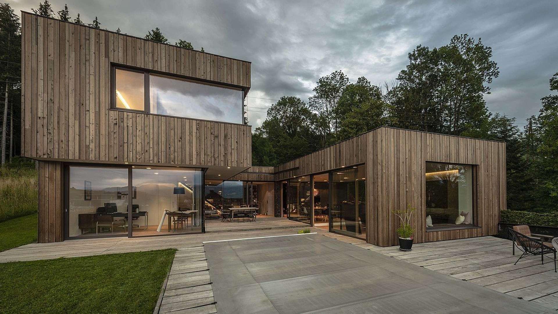 Holzhaus mit Holzalufenstern bei Dämmerung