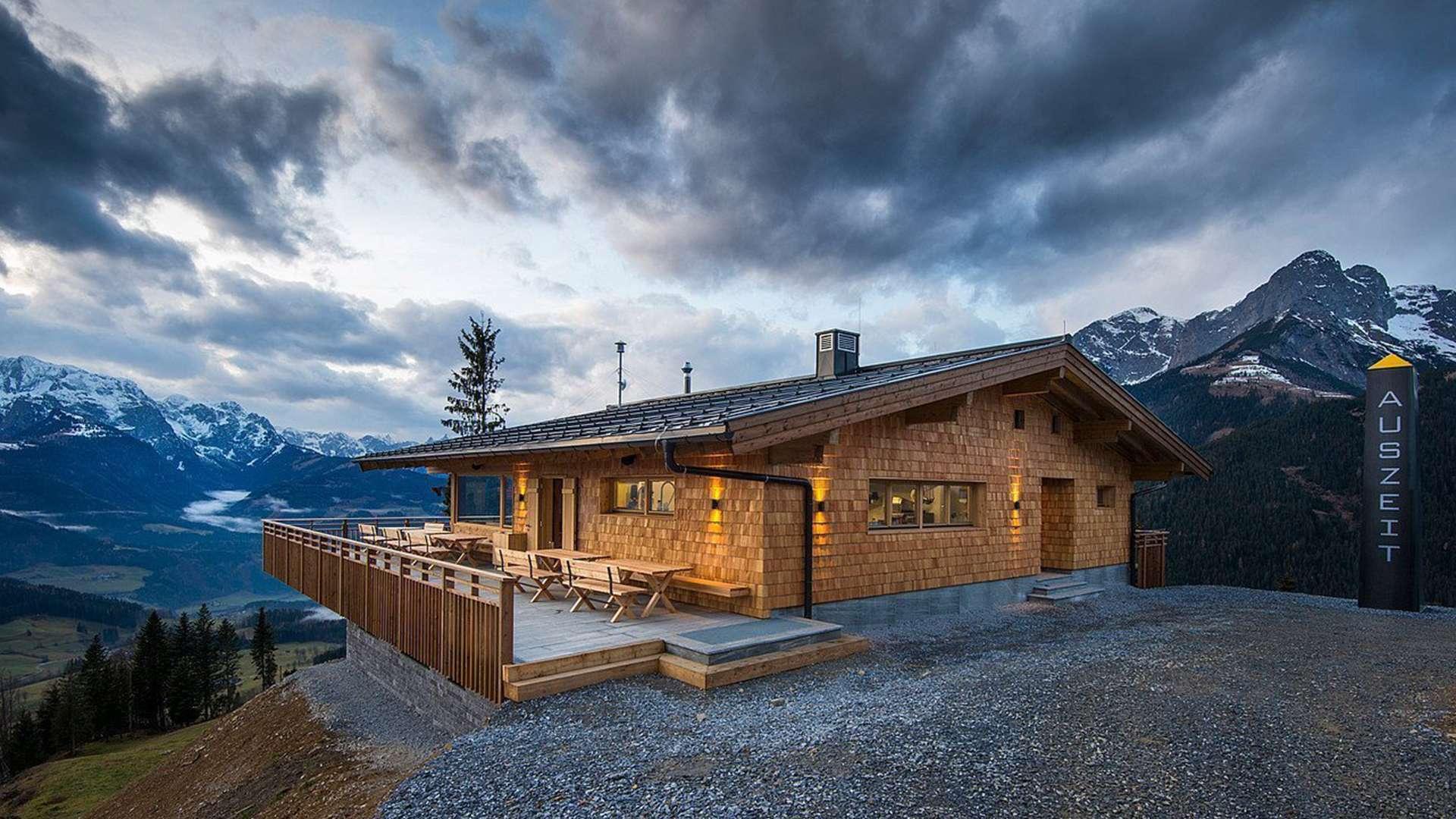 Holzhütte mit Holzfenstern auf einem Berg bei Dämmerung